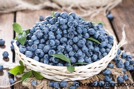 Big portion of fresh harvested Blueberries on wooden background (close-up shot)